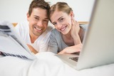 Happy couple on bed using laptop