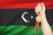 Medal in hand with flag on background - State of Libya