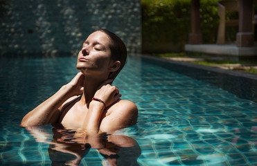 beautiful female model posing by the pool, outdoor portrait