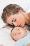 Mother sleeping with baby son on bed