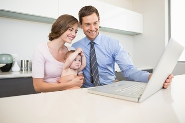 Parents using the laptop with their baby son at counter