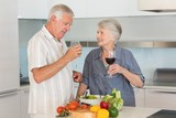 Smiling senior couple preparing a salad and having red wine