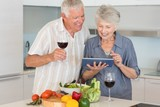 Smiling senior couple preparing a salad and using tablet pc