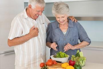 Smiling senior couple preparing a salad