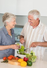 Smiling senior couple preparing a salad