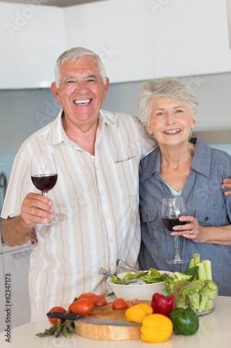 Smiling senior couple preparing a meal and having red wine