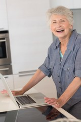 Happy senior woman using the laptop at the counter