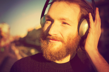 young stylish bearded man listening to music