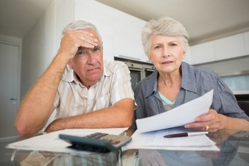 Worried couple paying their bills looking at camera