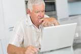 Puzzled senior man using the laptop at the table