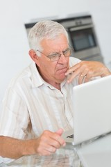 Focused senior man using the laptop at the table