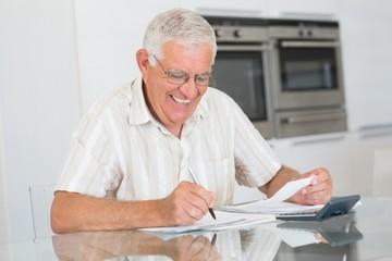 Focused senior man paying his bills