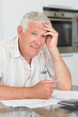 Worried senior man paying his bills