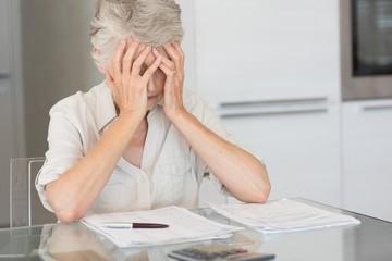 Worried senior woman paying her bills