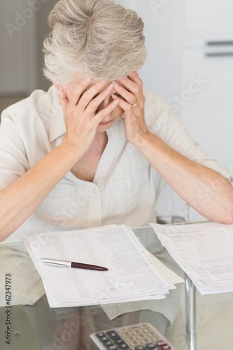 Worried senior woman paying her bills