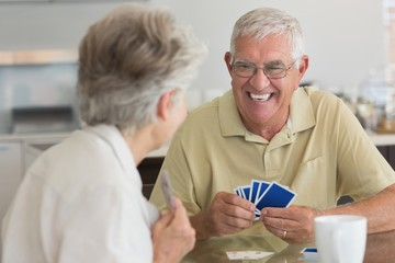 Happy senior couple playing a card game