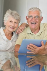 Happy senior couple using tablet pc at the table