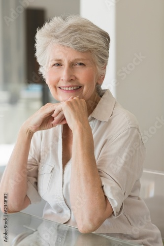 Happy senior woman sitting at the table