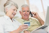 Happy senior couple paying online bill with laptop on the couch