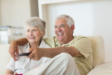 Happy senior couple watching tv on the couch
