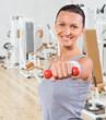 beautiful sportswoman with small dumbbell in the gym