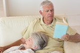 Senior man sitting on couch reading with partner resting on lap