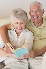 Senior couple sitting on couch reading together