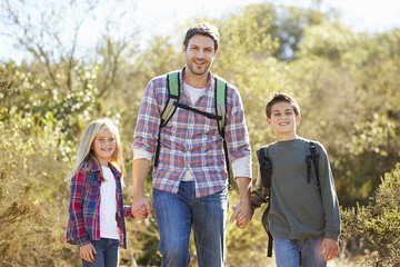 Father And Children Hiking In Countryside Wearing Backpacks