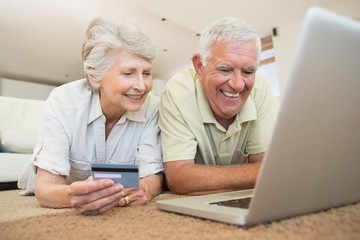 Cheerful senior couple using the laptop together lying on rug