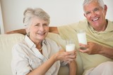 Senior couple having milk together on the couch