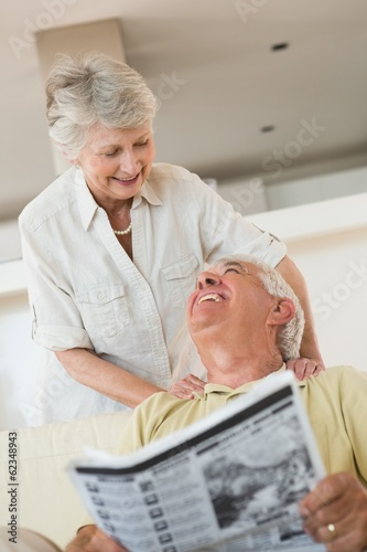 Senior man reading newspaper with partner leaning on shoulders