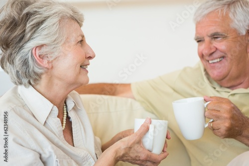 Senior couple having coffee together on the couch
