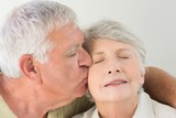 Senior woman getting a kiss on the cheek from partner