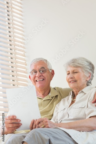 Senior couple looking at document together on the couch