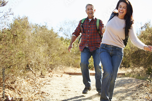 Couple Hiking In Countryside Wearing Backpacks - 62349162