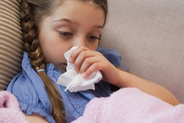 Young girl blowing nose with tissue paper