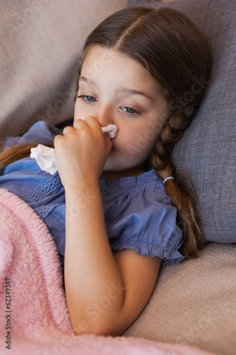 Close-up of a girl blowing nose with tissue paper