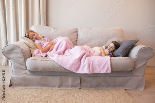 Two young girls sleeping on couch
