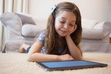 Close-up of a little girl using digital tablet in living room