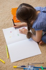 High angle view of a little girl drawing in living room