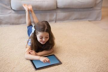 Full length of a little girl using digital tablet in living room