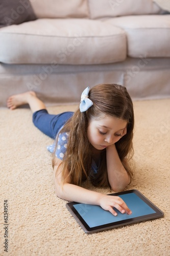 Full length of a girl using digital tablet in living room