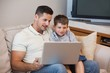Father with son using laptop in living room