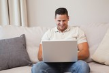 Smiling young man using laptop in living room