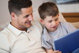 Father with son using digital tablet in living room