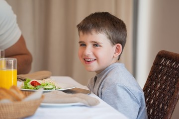 Smiling young boy sitting at dining table