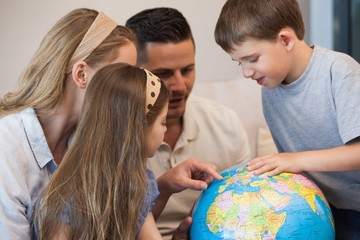 Close-up of a family of four looking at globe