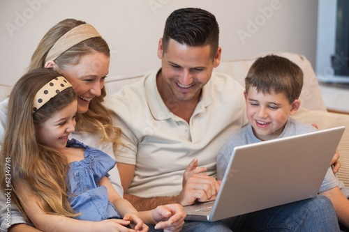 Happy family of four using laptop in living room