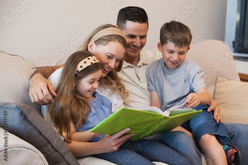 Family of four looking at album photo in living room