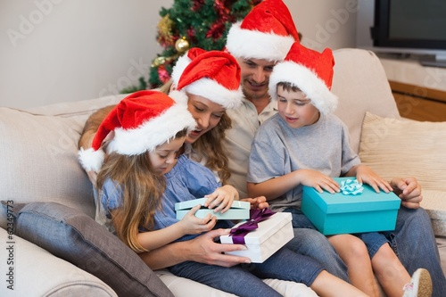 Family in santa hats sitting on sofa with gift boxes in living r
